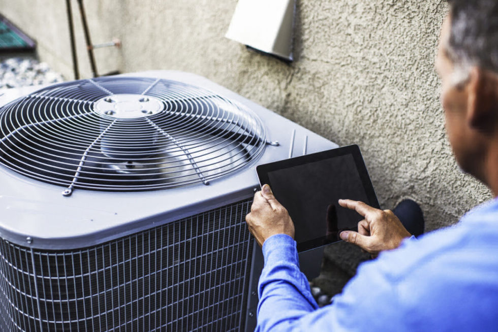 Home Inspector examining air conditioner