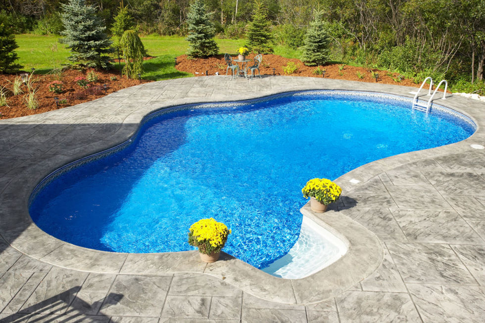Pretty blue pool with yellow flowers on decking